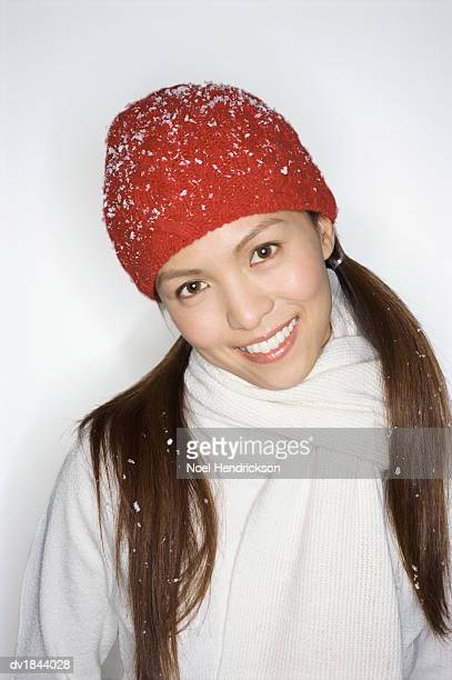 Studio Portrait of a Smiling Woman Wearing a Red Woolen Hat