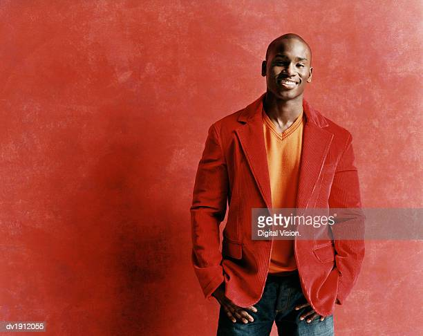 studio portrait of a smiling young man in a red jacket - red jacket stock pictures, royalty-free photos & images