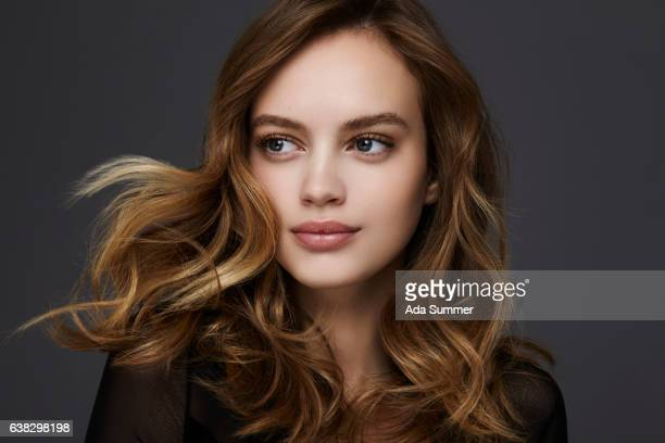 studio portrait of a stylish young brunette woman - wavy hair stock pictures, royalty-free photos & images