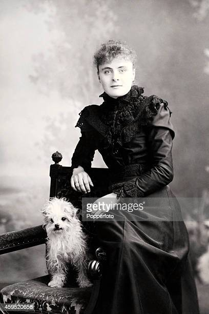 A studio portrait of a stylish young lady with her miniature dog circa 1890