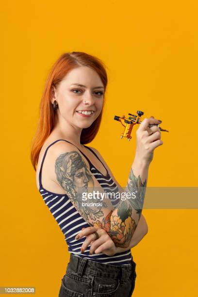studio portrait of a tattoo artist on a yellow background - female body piercing stock photos and pictures