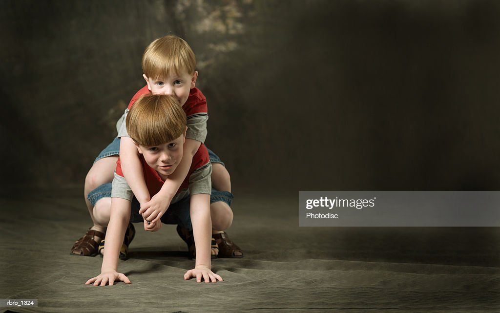studio portrait of a two caucasian redheaded brothers as they play and climb on each other : Stockfoto