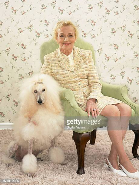 Studio Portrait of a Woman Wearing a Suit and Her Poodle Dog