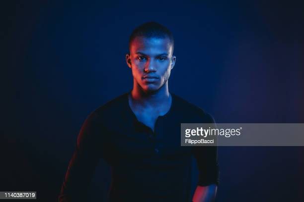 studio portrait of a young adult man with colorful lights - black stock pictures, royalty-free photos & images