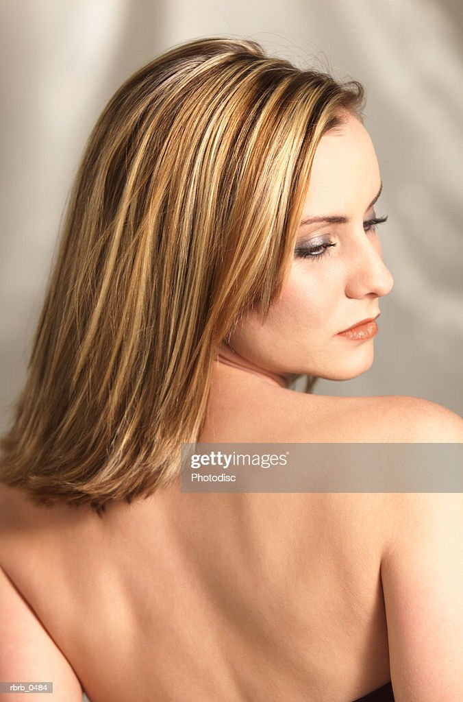 studio portrait of a young attractive caucasian blonde woman as she shows her bare back : Stockfoto