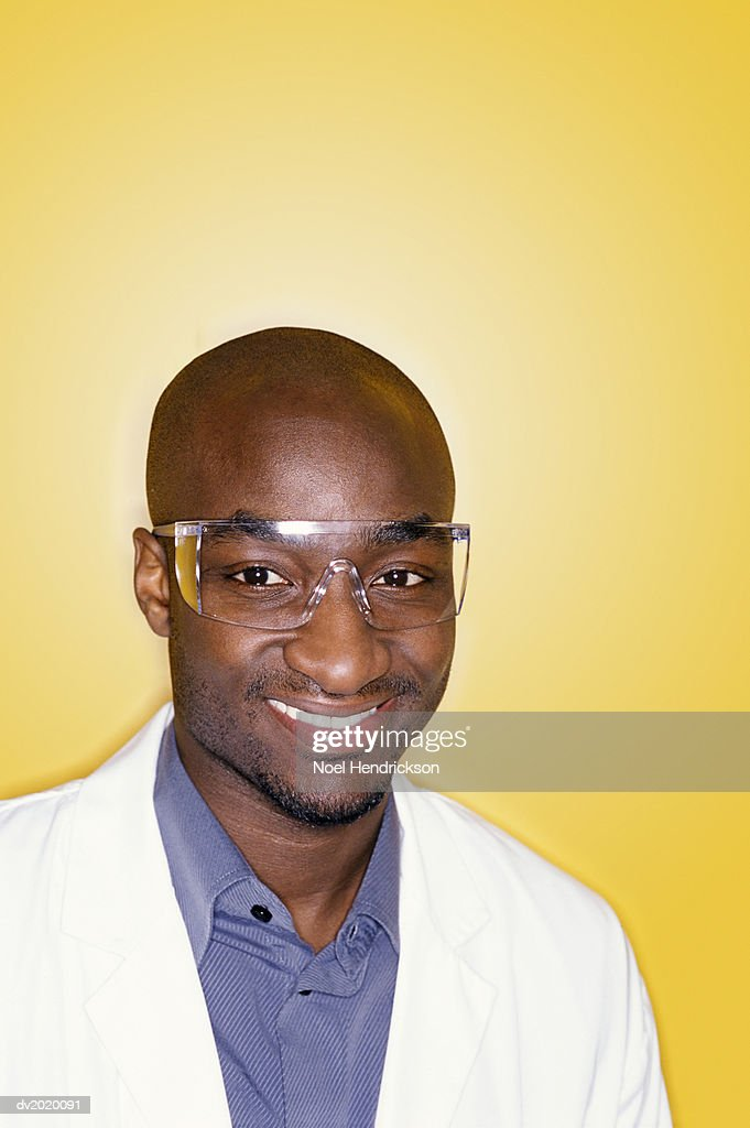 Studio Portrait of a Young Bald Man Wearing a Lab Coat and Safety Goggles : Stock Photo