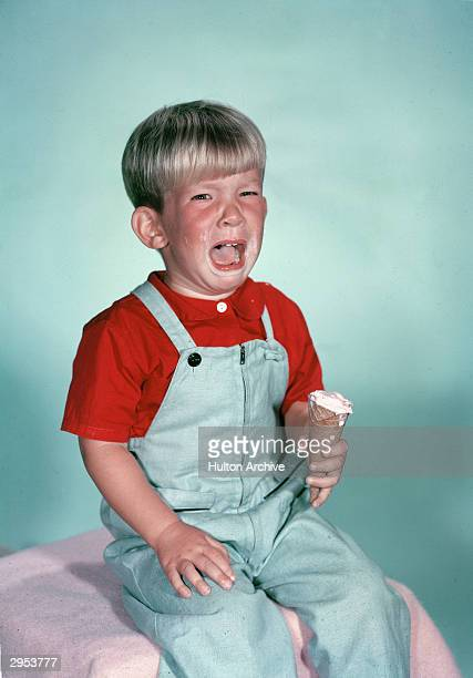 Studio portrait of a young boy crying as he holds a melting ice cream cone circa 1962