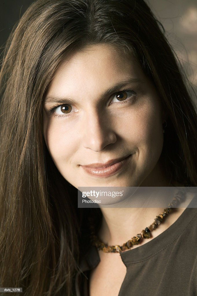 studio portrait of a young brunette woman in a brown shirt as she smiles seriously : Stockfoto