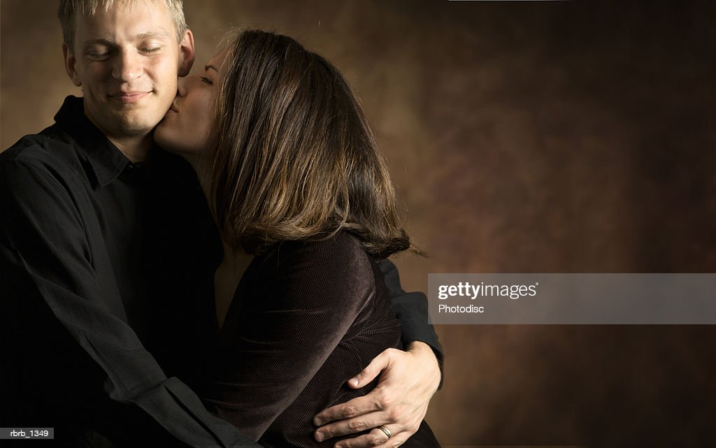 studio portrait of a young caucasian couple as the woman leans in and kisses the man : Stockfoto