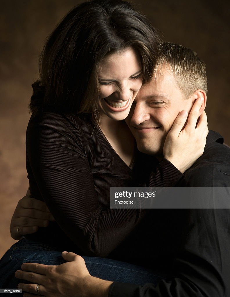 studio portrait of a young caucasian couple as the woman lovingly hugs the man as they laugh : Stockfoto