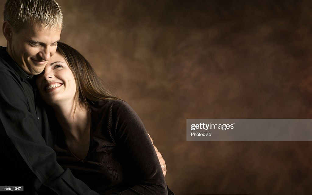 studio portrait of a young caucasian couple as they hold each other and laugh together : Stockfoto