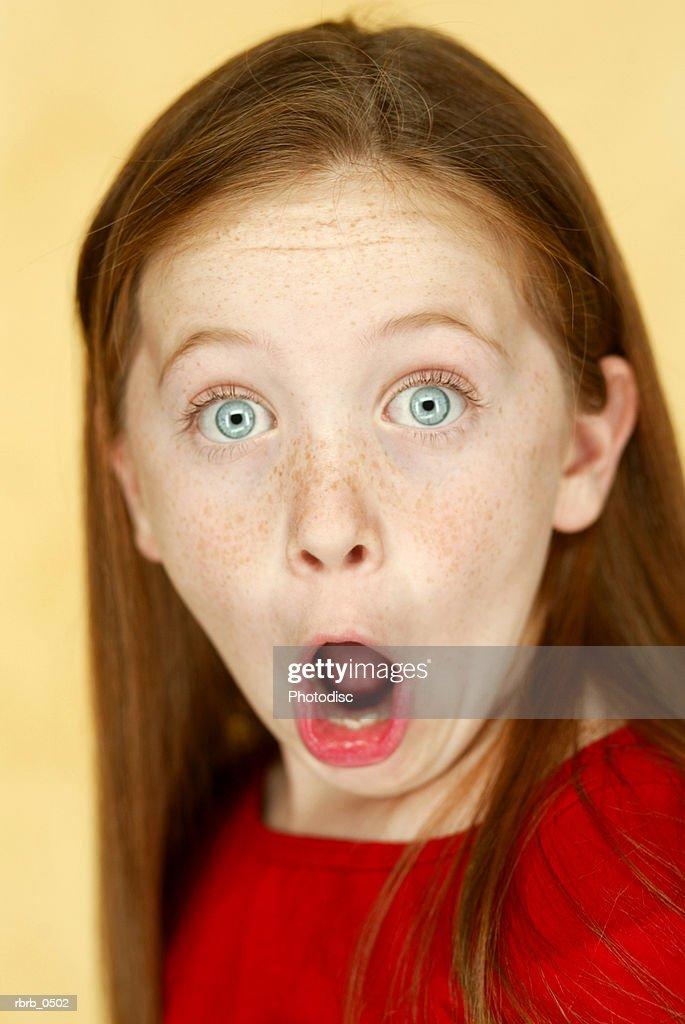 studio portrait of a young caucasian girl in a red shirt as she flashes a funny shocked face : Stockfoto