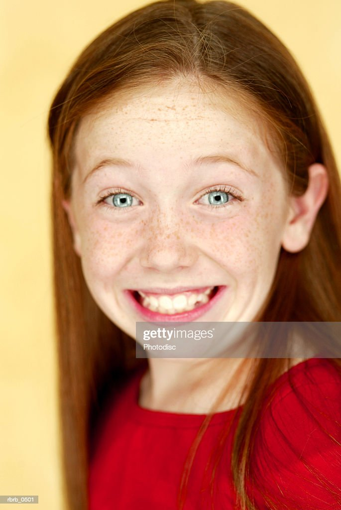 studio portrait of a young caucasian girl in a red shirt as she smiles : Stockfoto