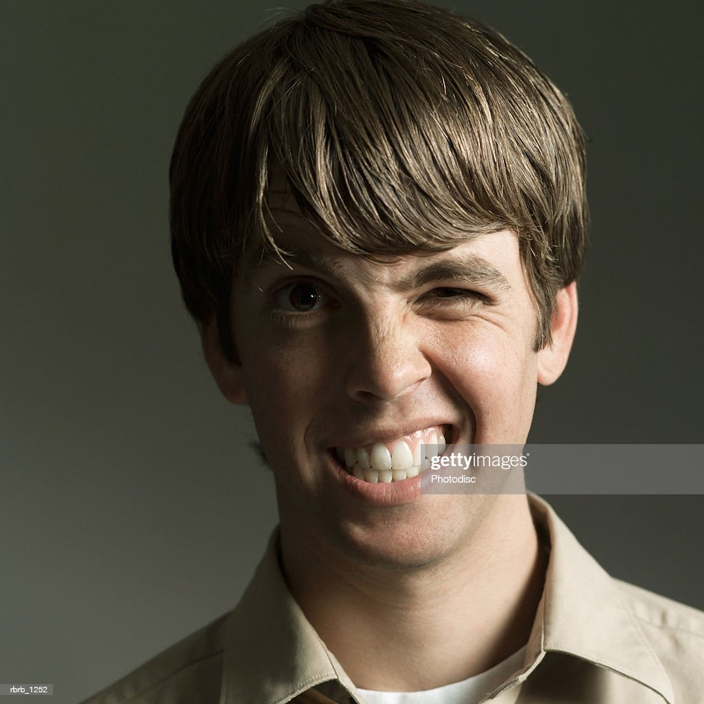 studio portrait of a young caucasian man in a tan shirt as he makes a funny face : Stockfoto