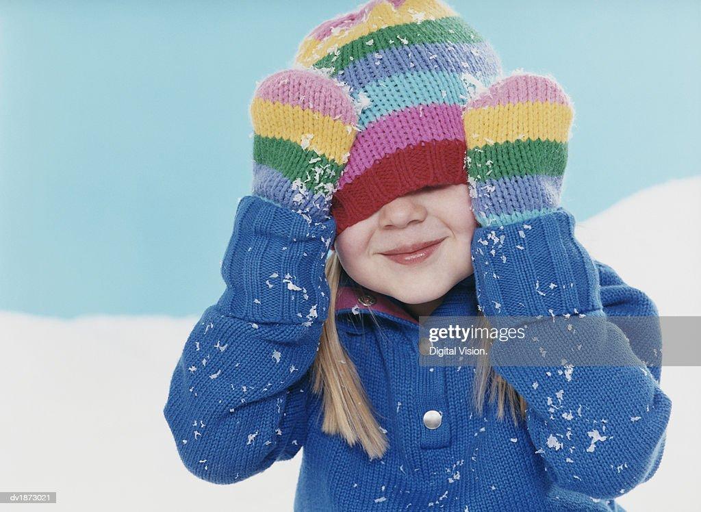 Studio Portrait of a Young Girl Hiding Under Her Woolen Hat : Stock Photo