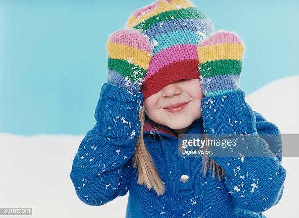 studio portrait of a young girl hiding under her woolen hat - mitten stock pictures, royalty-free photos & images