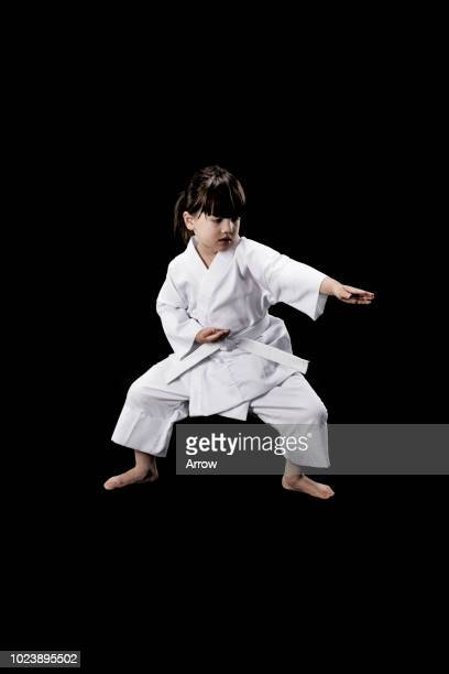 Studio portrait of a young girl practicing karate