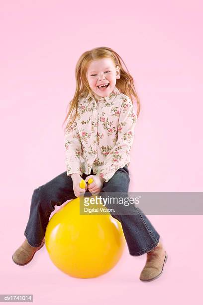 studio portrait of a young girl sitting on a space hopper - hoppity horse stock photos and pictures
