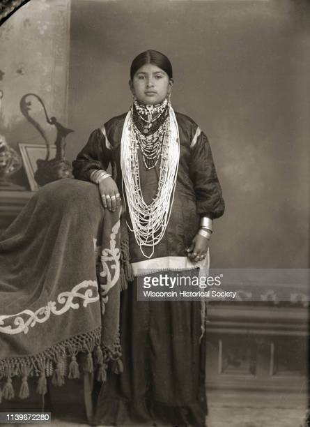 Studio portrait of a young HoChunk woman posing standing in front of a painted backdrop Black River Falls Wisconsin 1909 Her right arm is resting on...