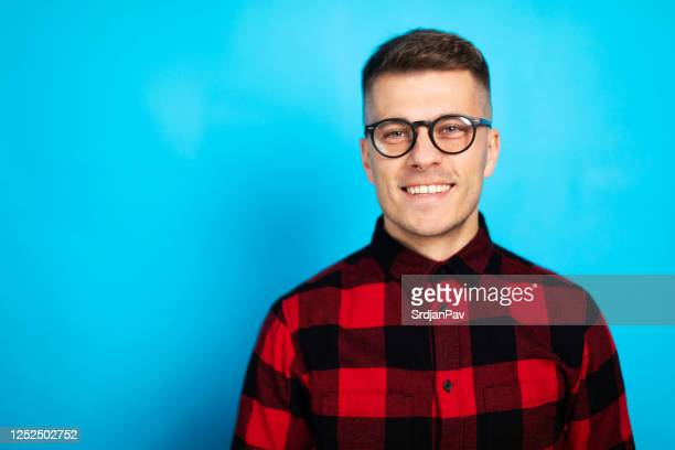 studio portrait of a young man posing against blue background - waist up stock pictures, royalty-free photos & images