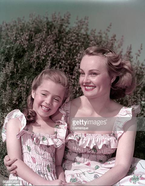 Studio portrait of a young mom and daughter dressed alike sitting outside Los Angeles California 1950
