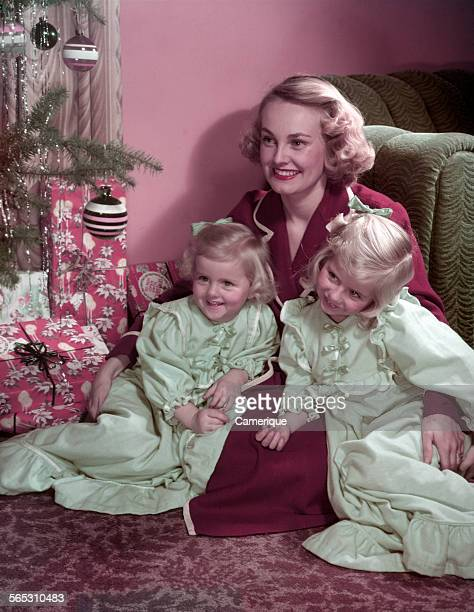 Studio portrait of a young mother sitting on the floor next to a Christmas tree holding two daughters in her lap Los Angeles California 1950