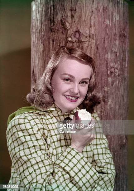Studio portrait of a young teen girl eating an apple while leaning on a tree Los Angeles California 1950