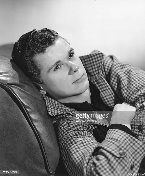 Studio portrait of actor Jackie Cooper reclining on a leather couch with his arms crossed wearing a checkered jacket for Paramount Pictures circa 1940