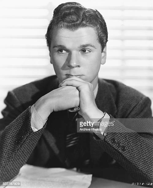 Studio portrait of actor Jackie Cooper sitting at a table wearing a suit and tie for Paramount Pictures circa 1940