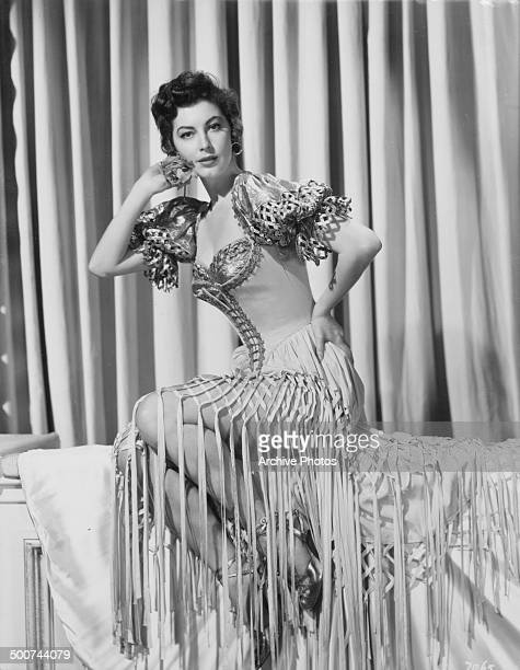 Studio portrait of actress Ava Gardner wearing a fringed dress and corset circa 1951