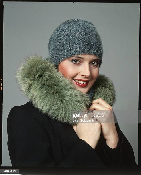 Studio portrait of actress Isabella Rossellini wearing a fur collared coat and a grey hat