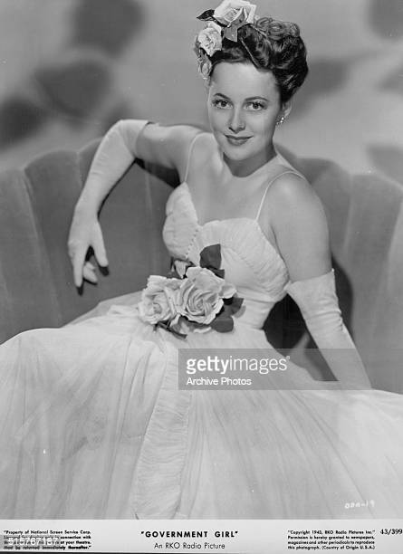 Studio portrait of actress Olivia de Havilland wearing a ball gown and flowers as she appears in the movie 'Government Girl' 1943