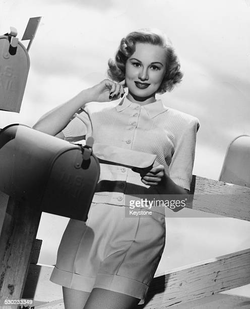 Studio portrait of actress Virginia Mayo leaning on a fence and reading mail from a mailbox circa 1945