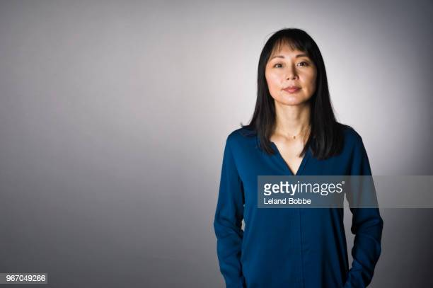 studio portrait of adult japanese woman with long dark hair - waist up stock pictures, royalty-free photos & images