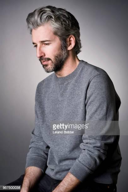 studio portrait of adult male with gray hair - blick nach unten stock-fotos und bilder