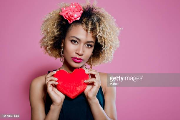 studio portrait of afro woman holding red heart - valentines african american stock pictures, royalty-free photos & images