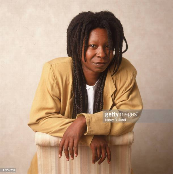 Studio portrait of American actor and comedian Whoopi Goldberg leaning on a chair, 1988.