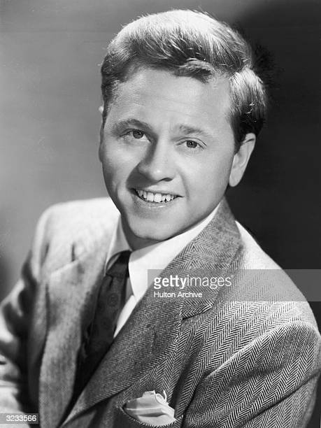 Studio portrait of American actor Mickey Rooney smiling in a suit