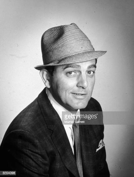 Studio portrait of American actor Mike Connors wearing a houndstooth hat and a plaid jacket Los Angeles California