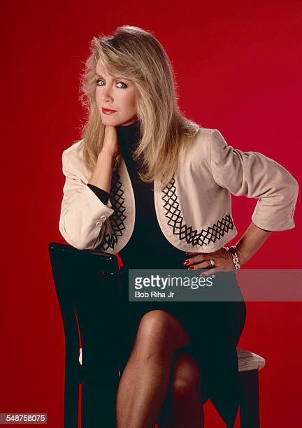 Studio portrait of American actress Donna Mills her hand on her chin as she poses against a red background Beverly Hills California March 18 1983