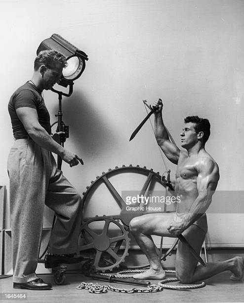 Studio portrait of American bodybuilder and physical fitness expert Jack La Lanne wearing a swimsuit taking directions from photographer Russ Warner...