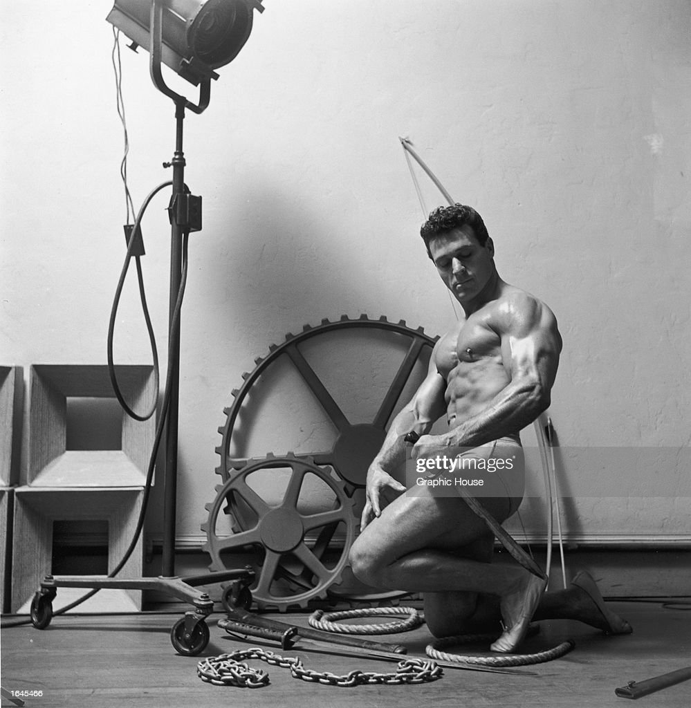 Studio portrait of American bodybuilder and physical fitness expert Jack La Lanne, wearing a swimsuit, holding a sword with other props in the background, 1953.