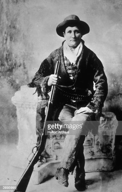 Studio portrait of American pioneer Calamity Jane wearing a fringed leather jacket leather pants and a cowboy hat holding a rifle while sitting with...