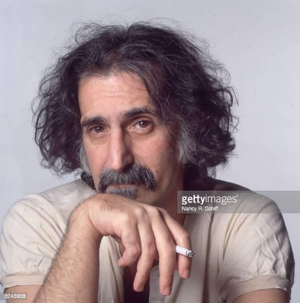 Studio portrait of American rock and roll musician Frank Zappa holding a cigarette