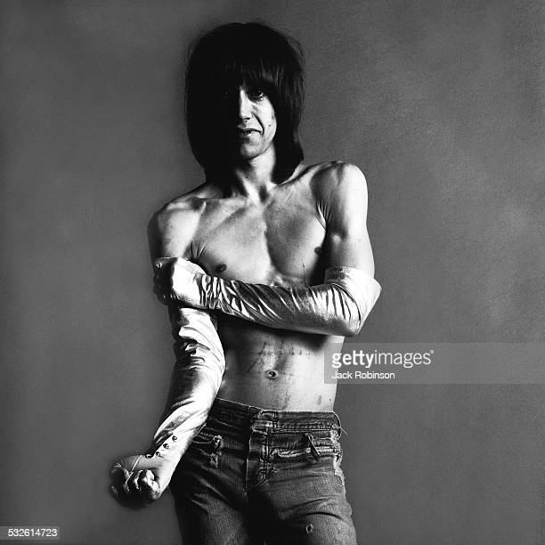 Studio portrait of American rock singer Iggy Pop of the group the Stooges barechested and in long satin gloves as he poses with one arm extended and...
