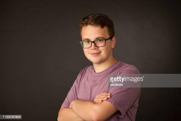 studio-porträt eines 18-jährigen mannes in brille und einem lila t-shirt auf schwarzem hintergrund - 18 19 jahre stock-fotos und bilder
