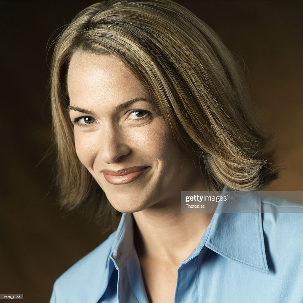 studio portrait of an adult caucasian blonde woman in a blue shirt as she smiles : Stockfoto