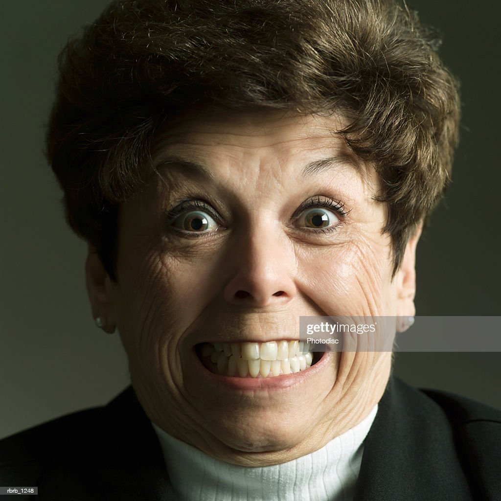 studio portrait of an adult caucasian brunette woman as she makes a funny shocked face : Stockfoto