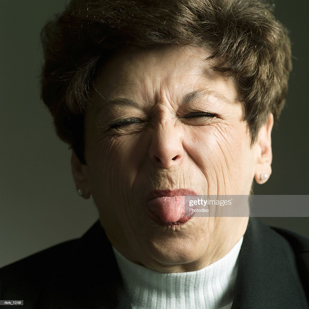 studio portrait of an adult caucasian brunette woman as she sticks her tongue out : Stockfoto