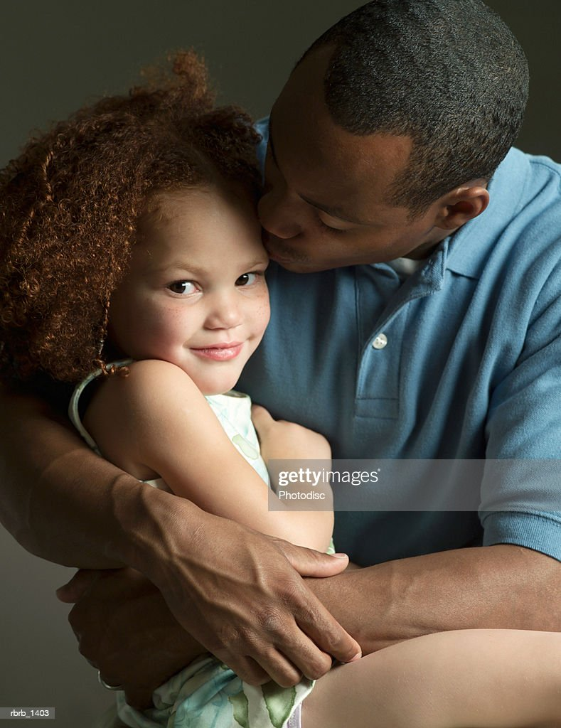 studio portrait of an african american father leaning in to give a kiss to his young daughter : Stockfoto